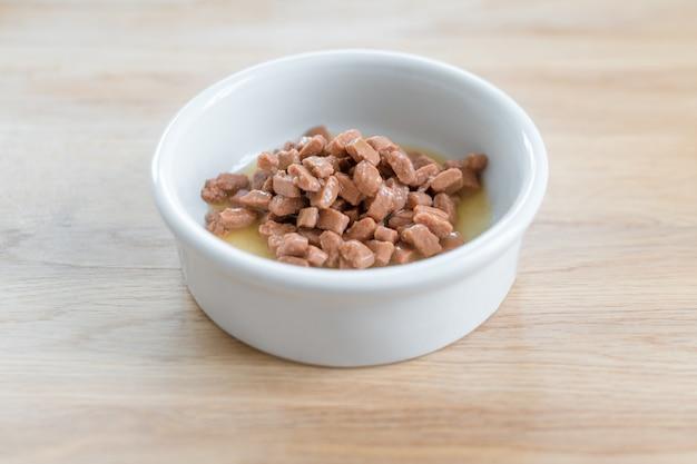 Comida úmida para cães e gatos em uma tigela branca no chão de madeira