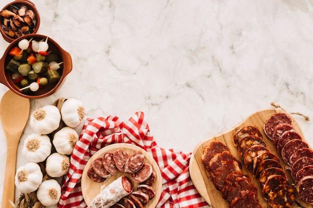 Comida variada perto de colher e guardanapo na mesa de mármore