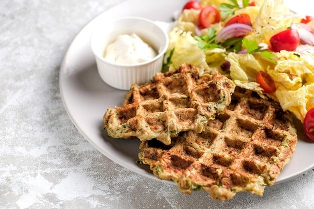 Comida vegetariana de waffles de vegetais com salada verde, tomate no prato