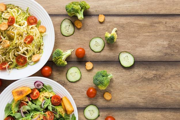 Comida vegetariana em pratos brancos com fundo de madeira