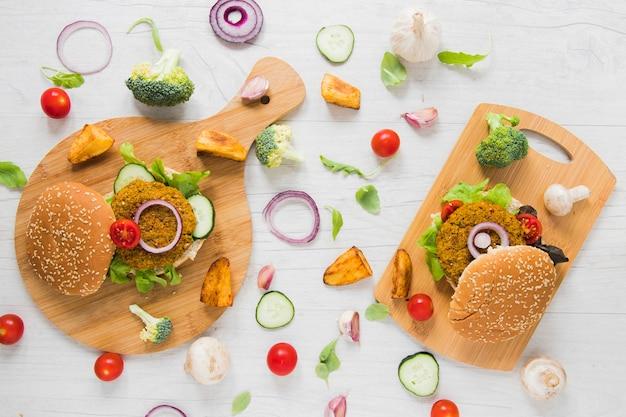 Comida vegetariana em tábuas na mesa de madeira branca