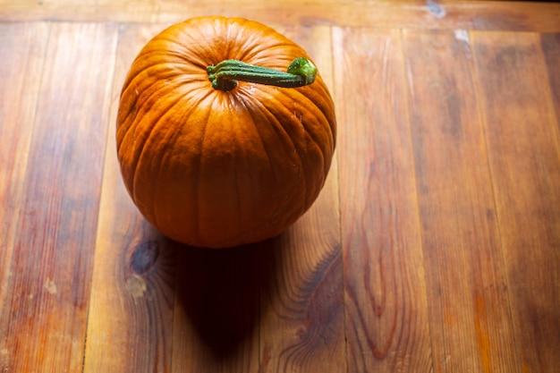 Comida vegetariana madura fresca e saudável com vitaminas abóbora laranja em uma mesa de madeira