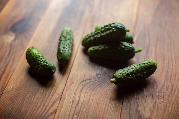 Comida vegetariana madura, fresca e saudável com vitaminas pepinos verdes repousam sobre uma superfície de madeira