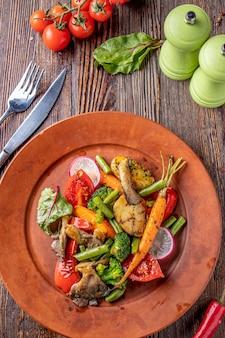 Comida vegetariana, prato de legumes e cogumelos cozidos, prato de restaurante, orientação vertical, vista superior