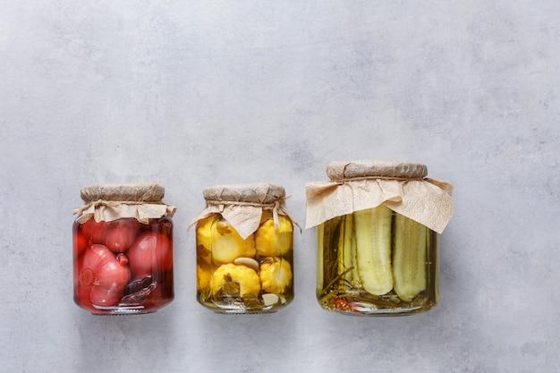 Comida vegetariana preservada fermentada em frascos de vidro. o conceito de comida enlatada. vista do topo.