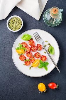 Comida vegetariana pronta para comer. tomates secos com manjericão, sementes de gergelim e abóbora em um prato em um fundo preto. vista superior e vertical