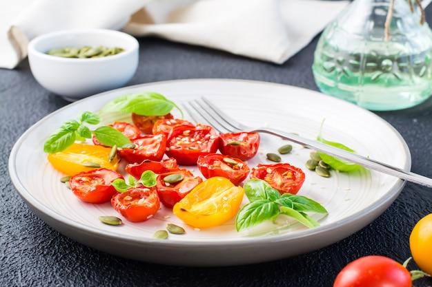 Comida vegetariana pronta para comer. tomates secos com manjericão, sementes de gergelim e abóbora em um prato sobre um fundo preto