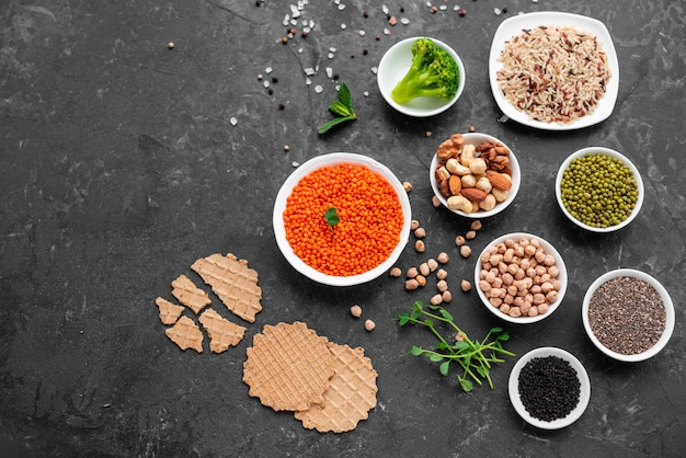 Comida vegetariana saudável em um fundo de concreto com espaço de cópia. nozes, feijões, verduras e sementes