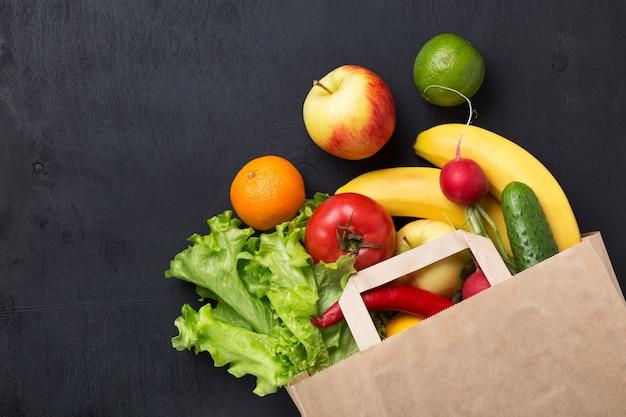 Comida vegetariana saudável em um saco de papel vegetais e frutas em um fundo escuro