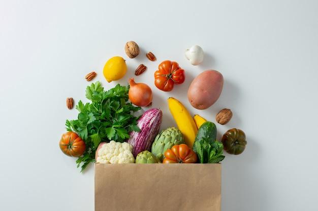 Comida vegetariana vegana saudável em saco de papel com vegetais e frutas em branco