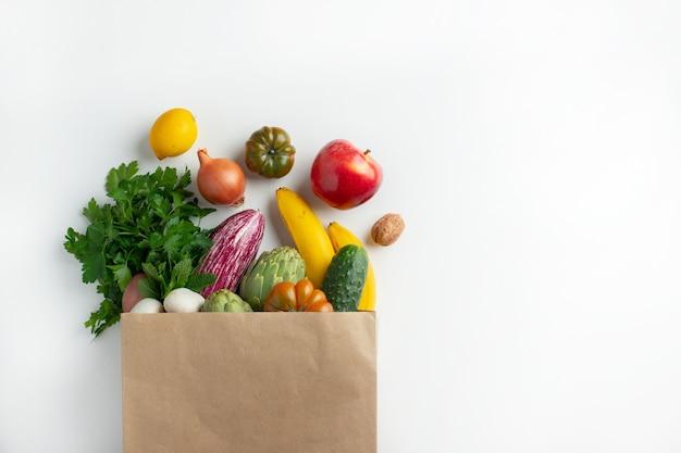 Comida vegetariana vegana saudável em vegetais de saco de papel e frutas em branco, copie o espaço. supermercado de alimentos de compras e conceito de alimentação vegana limpa.