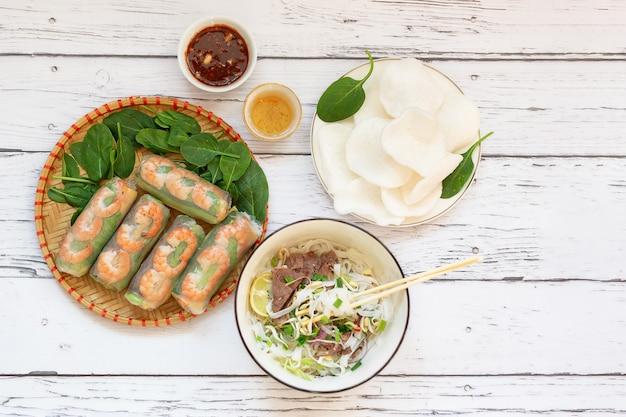 Comida vietnamita saudável close-up de rolinhos primavera pho bo sopa vietnamita com macarrão e chips de arroz bovino em uma placa de madeira molho de gergelim