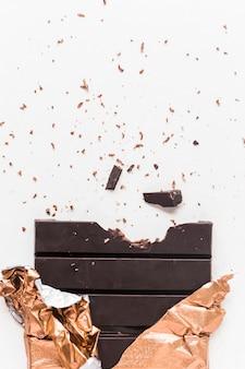 Comido barra de chocolate escura em embalagem dourada sobre fundo branco