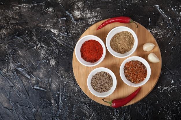Cominho de especiarias moídas, pimenta em xícaras de porcelana branca, alho e pimenta malagueta está em um suporte de madeira. copie spaes.