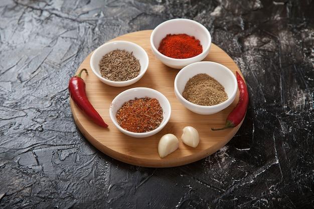 Cominho de especiarias moídas, pimenta em xícaras de porcelana branca, alho e pimenta malagueta está em um suporte de madeira.