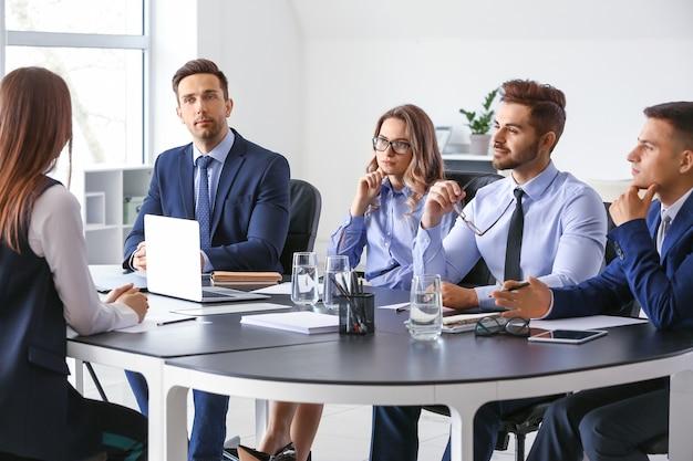 Comissão de recursos humanos entrevistando mulher no escritório