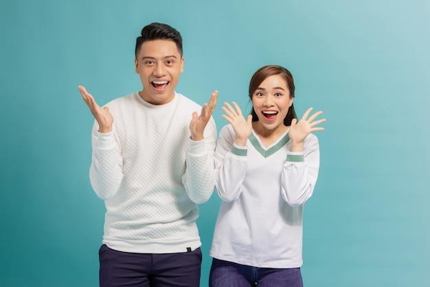Como duas ervilhas. um casal maravilhoso está posando com as palmas das mãos perto do queixo, olhando para a câmera com expressões faciais de surpresa