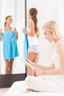 Como esse vestido me cabe? mulher jovem e bonita segurando um vestido e olhando no espelho enquanto outra mulher está sentada em primeiro plano e lendo uma revista