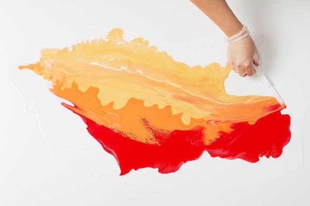 Como fazer pintura acrílica. trabalho em progresso. mão de mulher manchando a tinta com uma espátula.