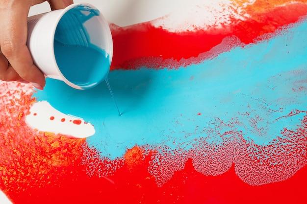 Como fazer pintura acrílica. trabalho em progresso. mão feminina segurando um copo de plástico com tinta azul.