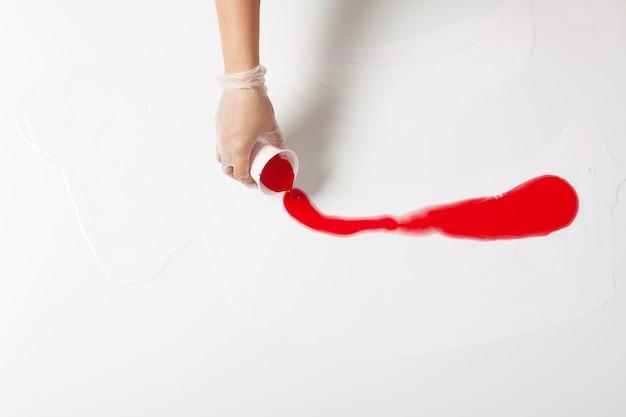 Como fazer pintura acrílica. trabalho em progresso. mão feminina segurando um copo de plástico com tinta vermelha.