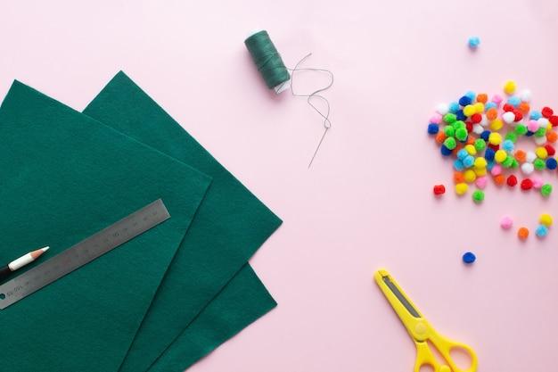Como fazer uma pequena árvore de natal de feltro em casa. instruções passo a passo. mãos facilitando o acompanhamento do projeto diy.