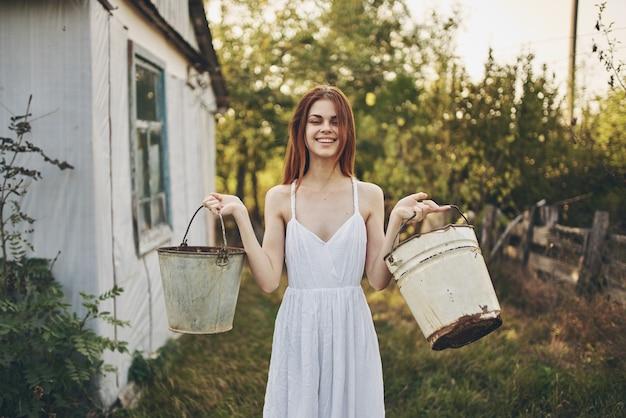Como foi uma mulher feliz com baldes perto de um prédio em uma vila de fazenda natural