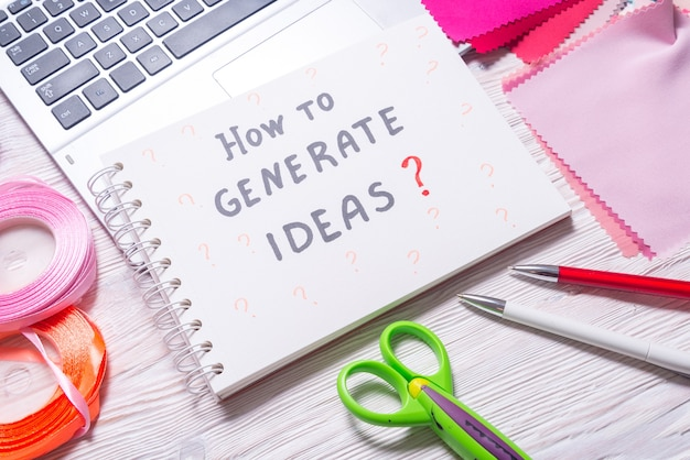 Como gerar ideias? mensagem no caderno sobre tecido e fita na mesa de trabalho da costureira
