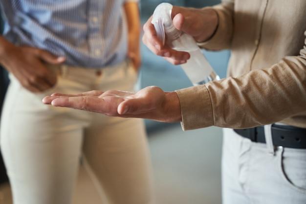 Como nova foto normal recortada de um trabalhador de escritório usando spray desinfetante para as mãos em pé com