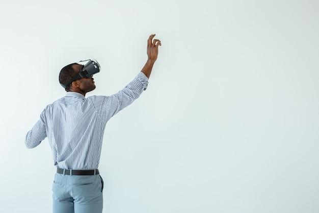 Como o processo, a visão traseira de um agradável empresário afro-americano escrevendo em um quadro virtual enquanto usa óculos de realidade virtual