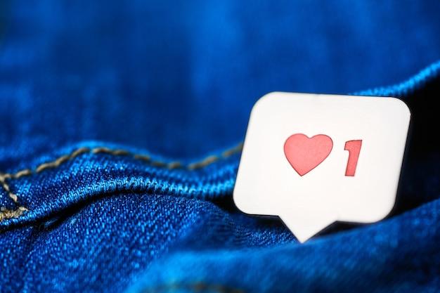 Como o símbolo do coração. como o botão de sinal, símbolo com coração e um dígito. marketing de rede de mídia social. fundo de textura de jeans azul.