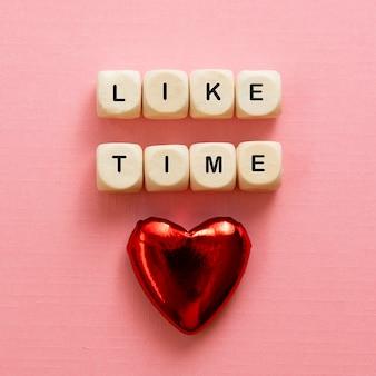 Como palavras de tempo, feitas de letras de madeira com coração vermelho em fundo rosa.