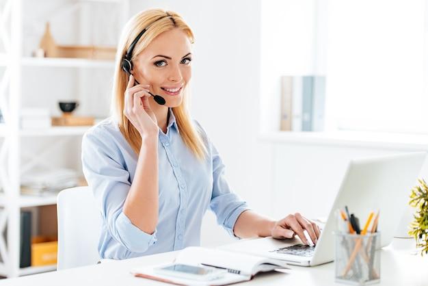 Como posso ajudá-lo? mulher jovem e bonita alegre em fones de ouvido, trabalhando no laptop e sorrindo enquanto está sentada em seu local de trabalho