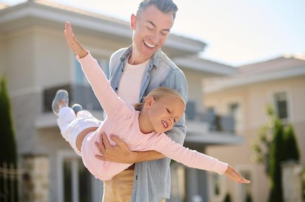 Como um avião. pai feliz segurando sua filhinha loira inspirada jogando um avião na rua em um belo dia quente