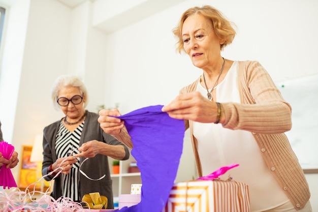 Como usá-lo. bela mulher idosa olhando para o papel de embrulho azul enquanto pensa em como usá-lo