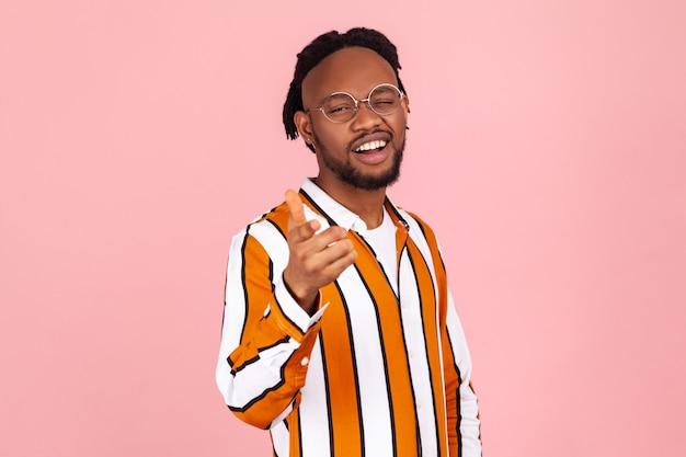 Como você está? homem afro-americano sorridente apontando o dedo para você e piscando