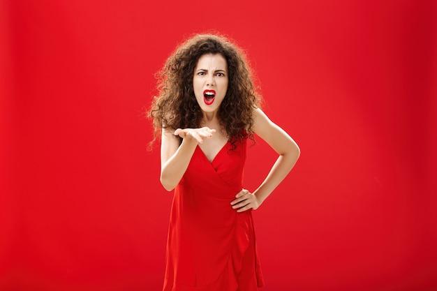 Como você ousa me trair. mulher adulta europeia indignada e indignada chateada com penteado encaracolado em um vestido elegante inclinando-se para a câmera com a palma da mão levantada, reclamando, culpando e julgando.