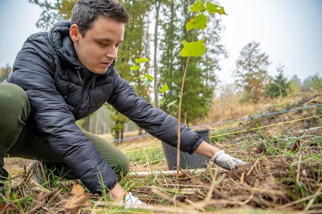 Como voluntário, o jovem planta árvores jovens para restaurar a floresta