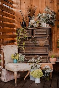 Cômoda antiga, decorada com várias flores e utensílios