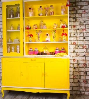 Cômoda galesa colorida em amarelo brilhante com prateleiras cheias de potes de vidro decorativos com ingredientes de cozinha e decorada com bengalas de doces listradas e fitas