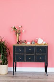 Cômoda velha com objetos em uma parede cor-de-rosa. o interior do quarto.