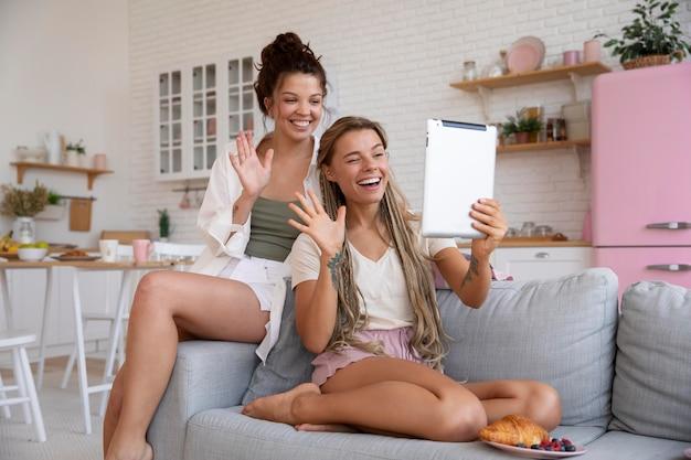 Companheiros de quarto sorridentes de tiro completo com tablet