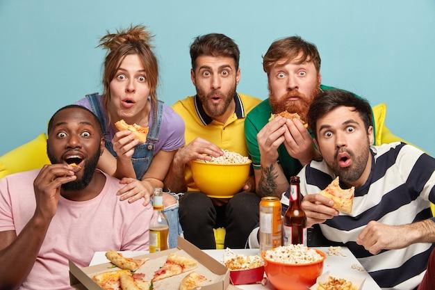 Companheiros engraçados multiétnicos comem pipoca, assistem a filmes de terror, olham com interesse, expressam surpresa, ficam assustados e assustados, isolados sobre uma parede azul, sentados em um sofá confortável