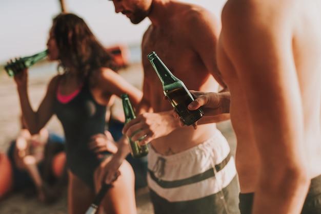 Companhia de adolescentes está bebendo cerveja.