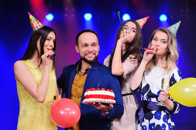 Companhia de amigos alegres em chapéus festivos para comemorar o evento