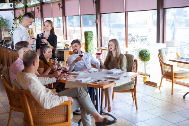 Companhia de amigos comemora reunião em um restaurante.