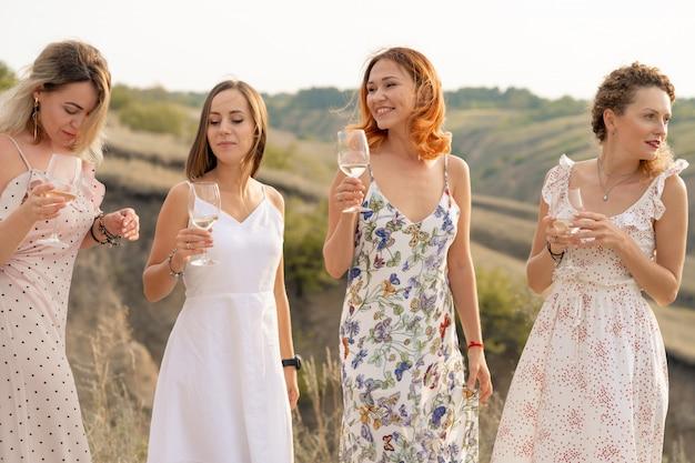Companhia de lindas amigas se divertindo e desfruta de um piquenique de verão verde, dançando e bebendo álcool.