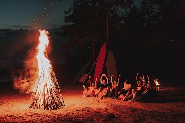 Companhia sente-se na frente da fogueira na praia