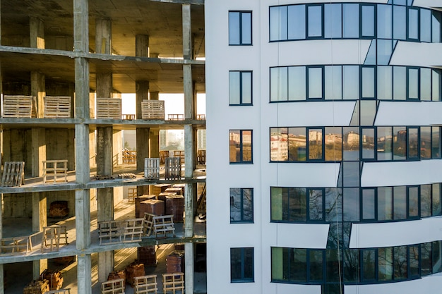 Comparação de close-up de alto edifício de apartamentos ou escritório moderno com várias janelas com janelas brilhantes e prédio inacabado em construção.