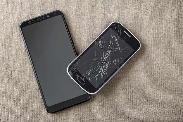 Comparação de dois celulares pretos, celular antigo com tela rachada e novo e moderno no fundo do espaço da cópia de pano claro. progresso da tecnologia e conceito de substituição.